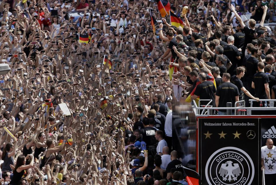 The team climbed aboard an open top truck for the last part of the trip to the Brandenburg Gate, inching its way forward through cheering crowds
