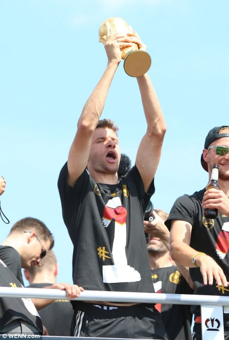 Thomas Müller lifts the World Cup trophy as an estimated 400,000 supporters pack the 'fan mile' in front of Berlin's landmark Brandenburg Gate