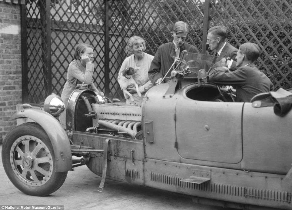 A group of people stand and chat around a Bugatti type 43, while a mechanic gets to work on the vehicle's engine