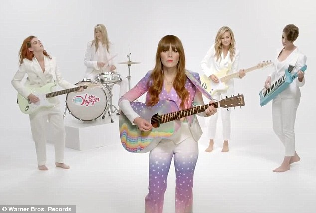 ABBA-esque: The clips begins with Kristin, Anne Hathaway, and Brie Larson flanking singer Jenny Lewis clad in white suits and going barefoot on the stark sound stage, with the songstress standing front and centre