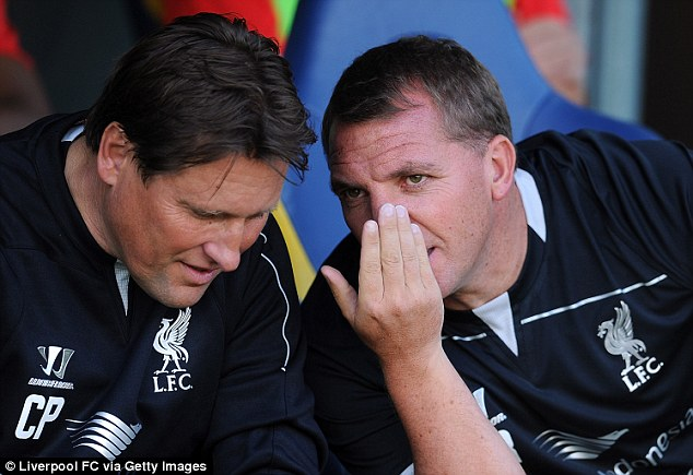Careful whispers: Liverpool boss Brendan Rodgers talks to assistant Colin Pascoe
