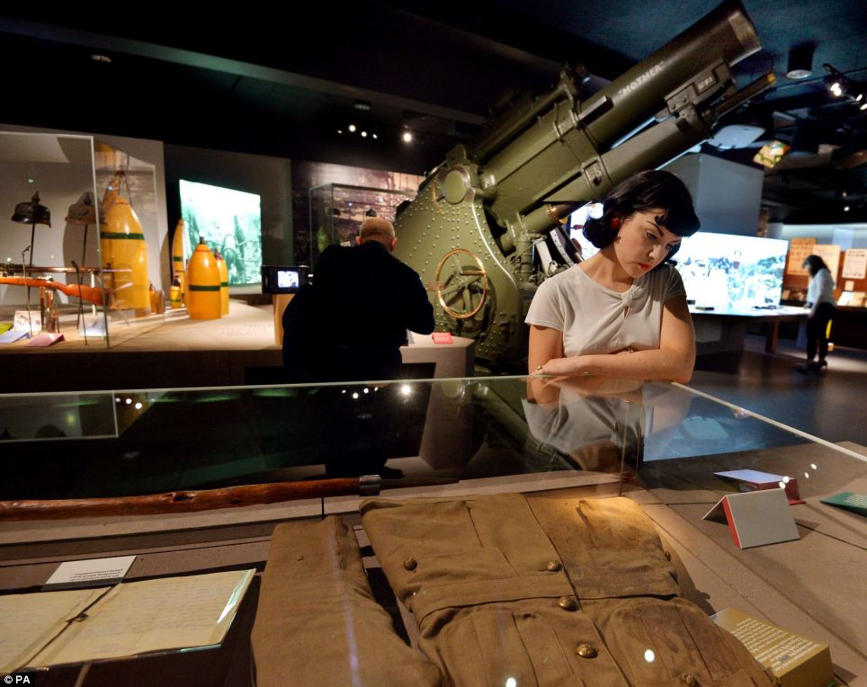 An artillery cannon looms over a young woman looking at a new display featuring a soldier's uniform in the new First World War Gallery. It's hoped the new gallery will help visitors understand how the war started and its global impact