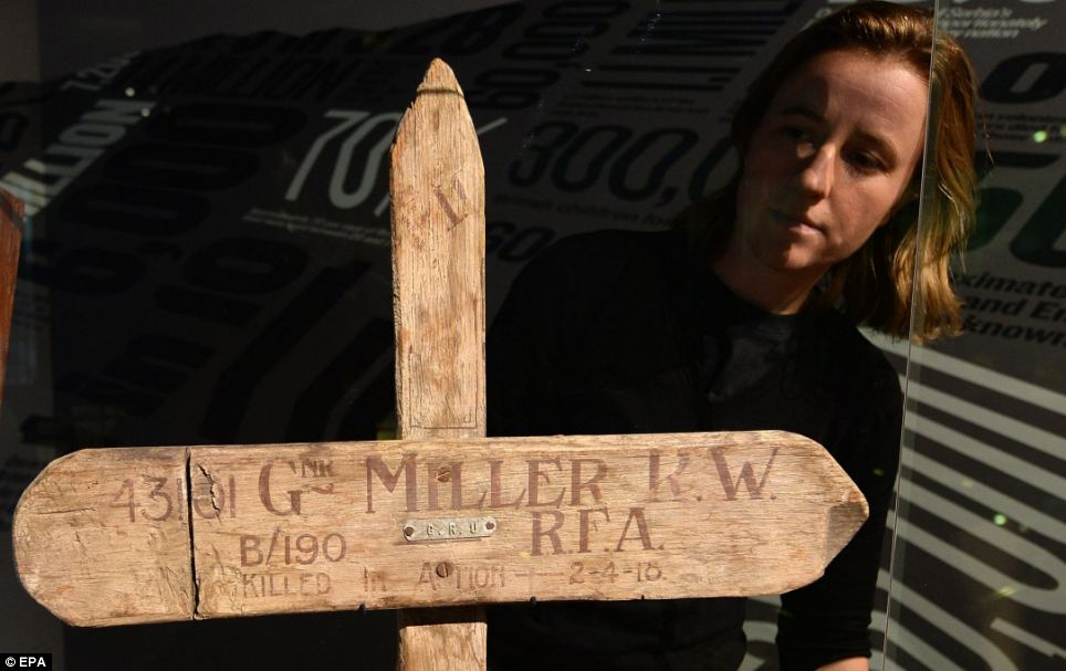 A staff member looks over a real First World War wooden cross. It was one of many used to mark temporary graves during the war, which saw millions killed