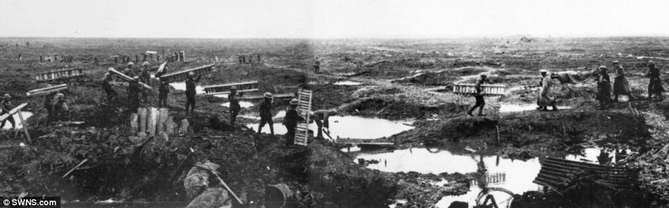 This image shows the aftermath of conflict at Passchendaele, Belgium. A long line of soldiers carry duckboards towards new positions and use them to cross the mud and flooded shell craters on the tortured ground