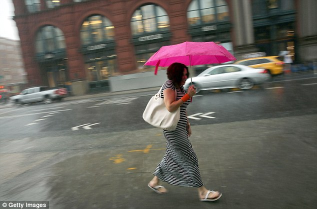 New Yorkers ran for cover after the rains began to swamp the city - leaving traffic delayed and many millions of commuters soaked