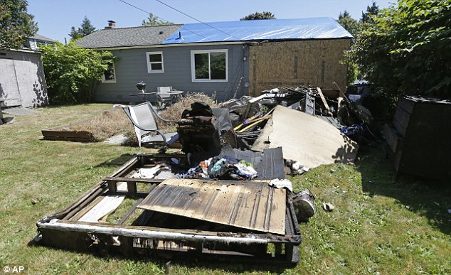 Debris: A tarpaulin has been pulled over the house roof and charred furniture has been dragged outside as the owners survey the damage