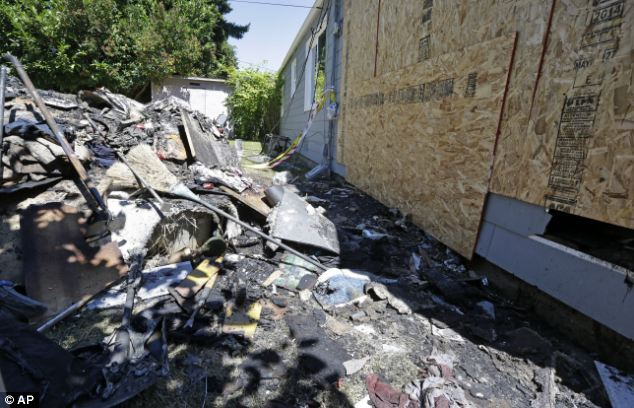 Debris has been piled in the backyard after a blaze broke out during a failed attempt to catch a spider