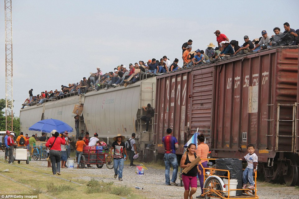 Central American immigrant get on the so-called La Bestia (The Beast) cargo train, in an attempt to reach the Mexico-US border, in Arriaga, Chiapas state, Mexico on July 16, 2014.  AFP PHOTO/ELIZABETH RUIZELIZABETH RUIZ/AFP/Getty Images