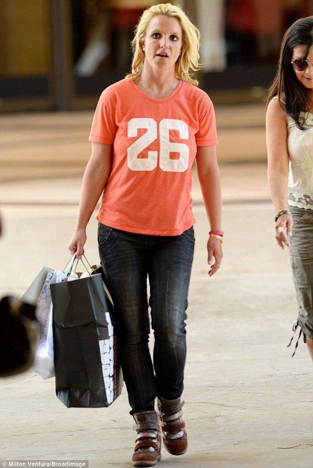 Pop of colour: The songstress sported a vibrant orange shirt with her jeans and hidden wedge sneakers
