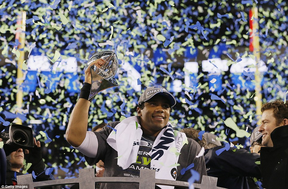 Champion: Seahawks quarterback Russell Wilson holds the famous Vince Lomabardi trophy aloft after his side triumphed in Super Bowl XLVIII against Denver