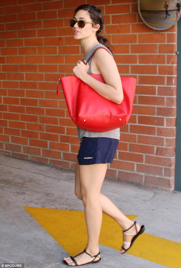 Keeping cool: Emmy carried a chic red bag and had changed out of her running shoes into a cute pair of sandals to make her way outside
