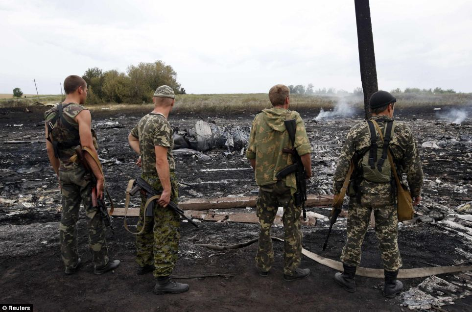 Airliner downed: Assault rifles in hand, four pro-Russian separatists survey the smouldering wreckage of a passenger jet destryoed by a missile in war-torn Ukraine