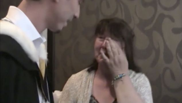 Proud moment: Ms Blair cries in disbelief as her son, dressed in his graduation gown, reveals his big secret