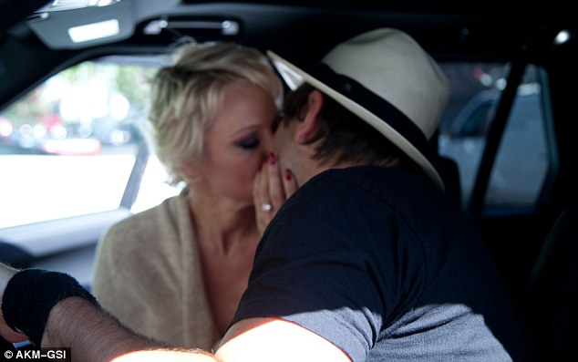 More smooching: They were also seen locking lips in the front seat of a vehicle