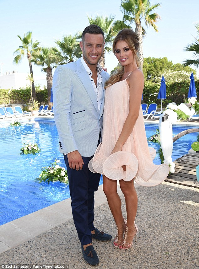 New romance: Elliott Wright and Chloe Sims cuddle up to one another at his sister Leah's wedding in Alicante, Spain on Thursday