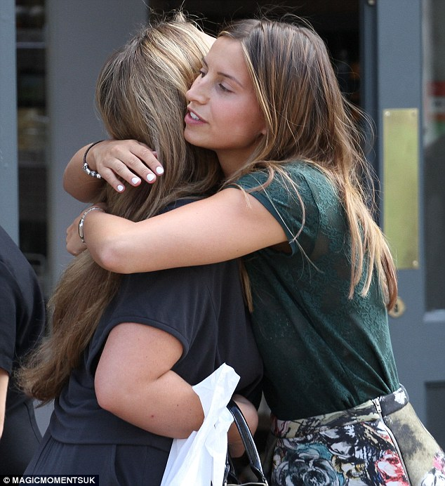 Close: The two friends greets one another with a hug after crossing paths outside new business Charlie's Deli