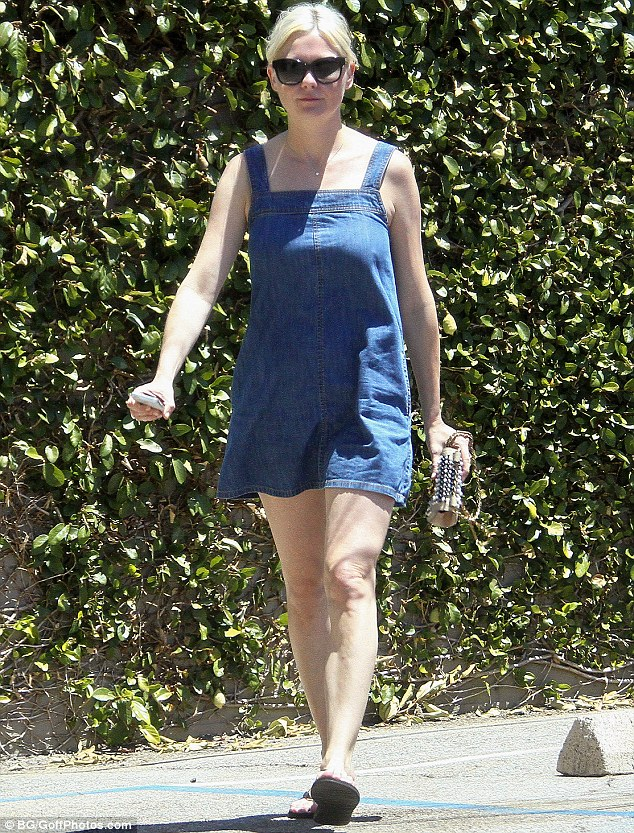 Damsel in denim: Kirsten Dunst showed off her lean limbs in a dungaree dress as she took a stroll in Los Angeles on Thursday