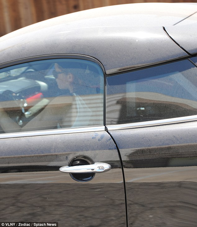 Cruising: The Twilight star's black and red Mini Cooper coupe appeared to be covered in dust as she left the workout facility