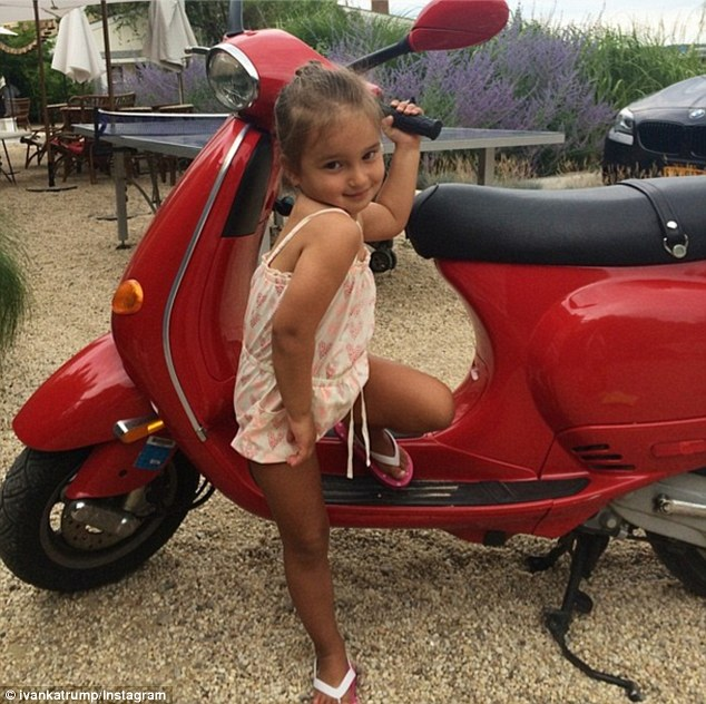 Styling: Arabella, who bears a striking resemblance to both parents, showed off her summer tan as she posed on a red scooter