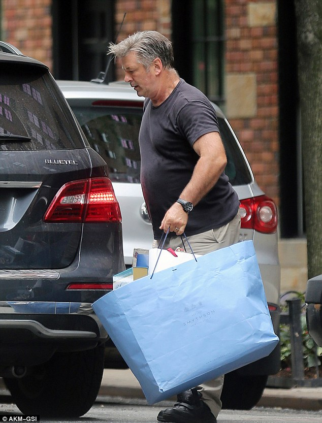 Dutiful: Alec, 56, is laden with bags as he is seen packing the car last week. He and Hilaria celebrated their second wedding anniversary on June 30