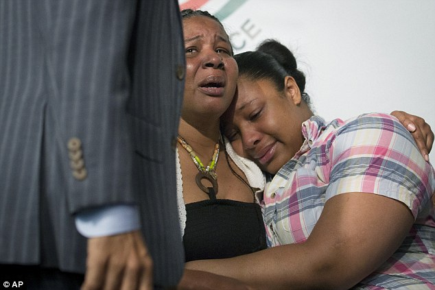 Grief: Esaw comforts Emerald, one of her and Eric's six children, during a press conference with the Rev Al Sharpton on Saturday