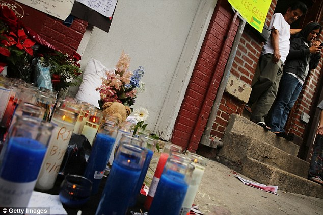 Memorial: Prayer candles, flowers and messages are left at the spot where Garner was arrested before his death