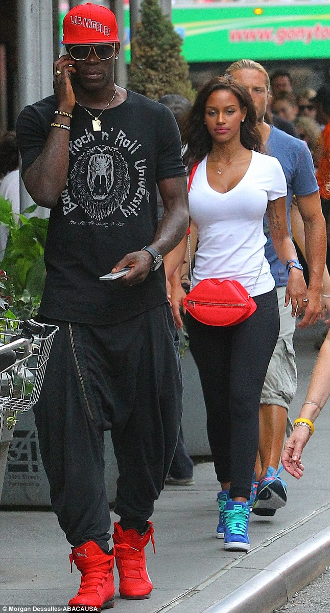 Walk and talk: Mario was spotted on the phone whilst carrying another as he walked the streets with fiance Fanny in New York