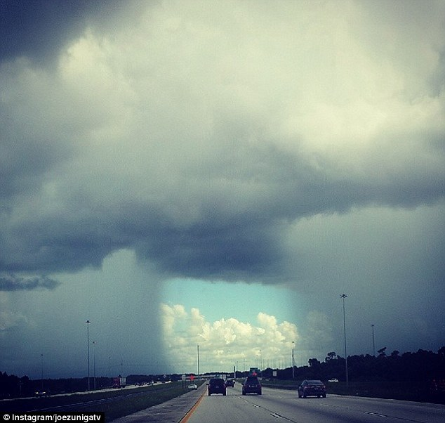 Parting: Joe Zuniga's photo, taken on Tuesday, shows a sunny center section of I-75 in Florida as it rains on either side