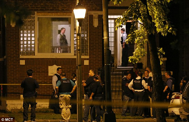 On the scene: Police officers and detectives gather Friday night at the home where Adams was shot during a sleepover