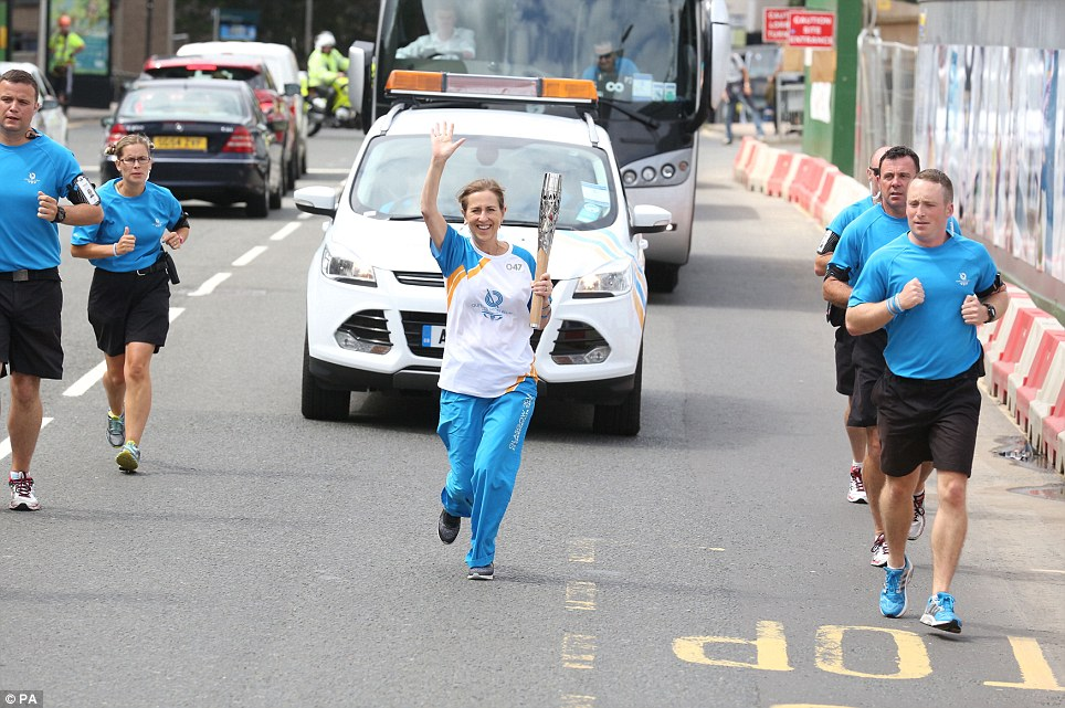 On the run: Batonbearer 047, broadcaster Kirsty Wark, carries the Glasgow 2014 Queen's Baton through George Square in Glasgow