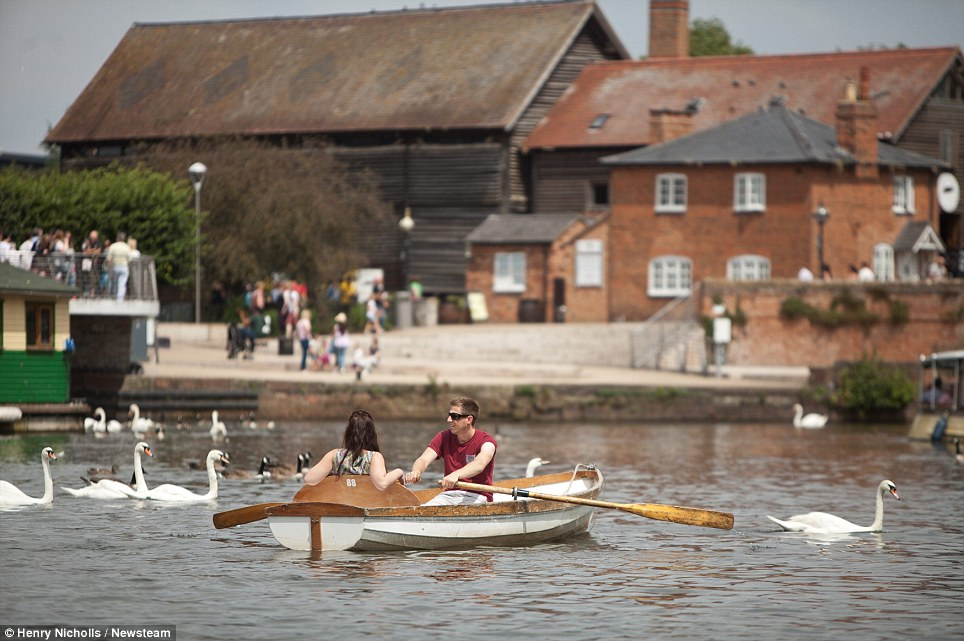 Pretty scene: People are seen in Stratford-upon-Avon, Warwickshire, as a forecaster declared that the worst of the bad weather was over