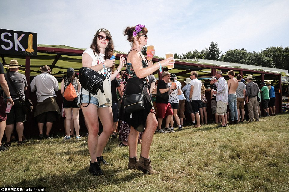 Flowers in her hair: Two young women get into the party spirit at the Latitude 2014 festival in Southwold, Suffolk