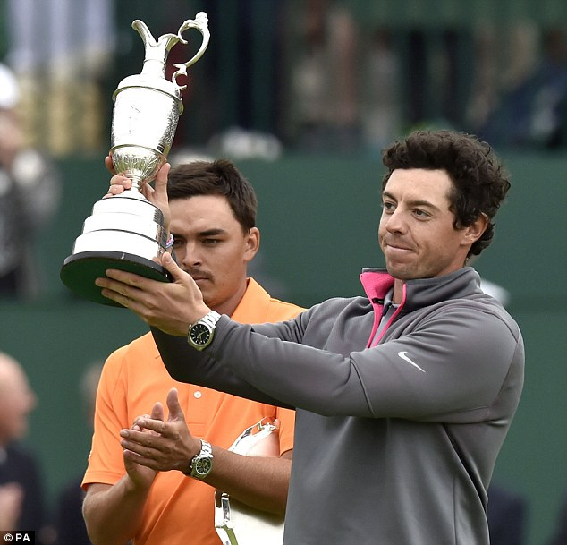 Aloft: Rory McIlroy holds the Claret Jug after winning the Open Championship on Sunday