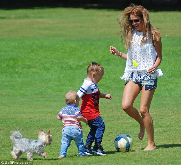 Family time: Danielle O'Hara plays football with her sons Archie (centre) and George