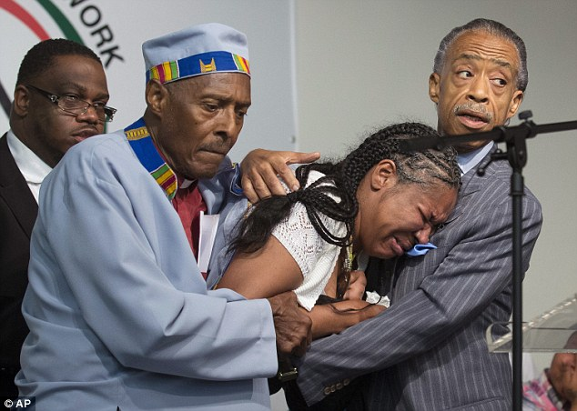 Esaw Garner, wife of Eric Garner, breaks down in the arms of Rev. Herbert Daughtry, center, and Rev. Al Sharpton during a rally and memorial service on Saturday