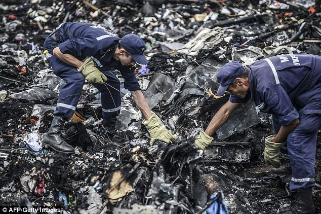Ukrainian State Emergency Service employees search for bodies among the wreckage at the crash site of Malaysia Airlines Flight MH17, near the village of Grabove