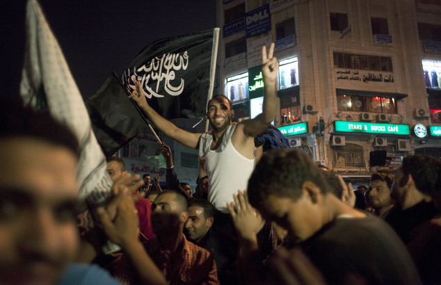 Palestinians dance while flying a Palestinian Islamic Jihad Movement flag reading in Arabic 'there is only one God and Muhammad is his prophet' during celebrations in the West bank city of Ramallah on Sunday