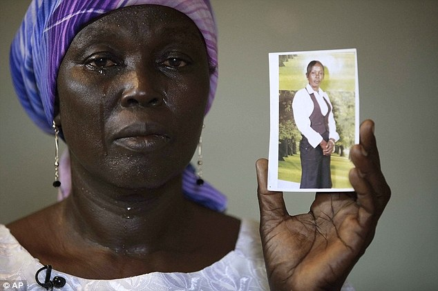 Martha Mark, the mother of kidnapped schoolgirl Monica Mark cries as she displays a photo of her missing daughter