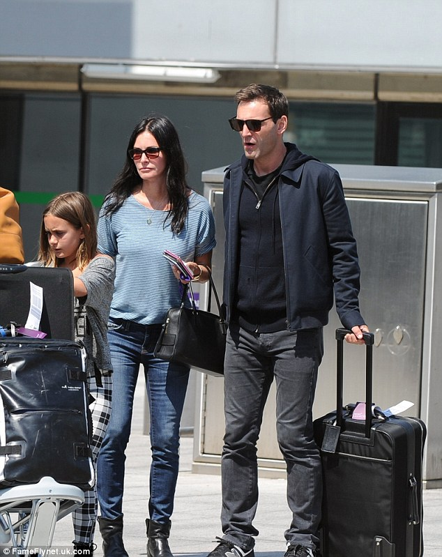Flying in style: Courtney looked effortlessly stylish in a casual ensemble, which saw her team a striped top with skinny jeans and black ankle boots