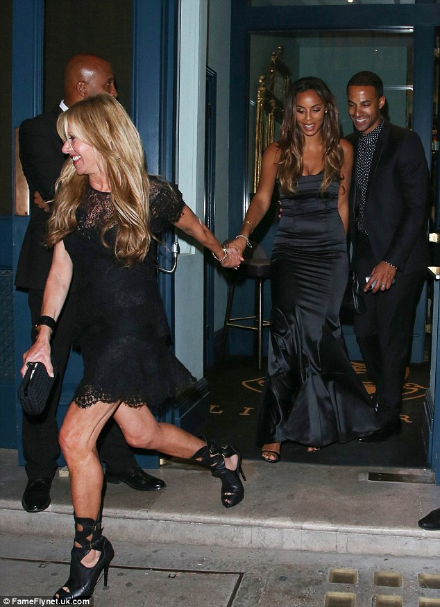 Glamorous pair: Rochelle is lead from the posh private members club where she celebrated Cheryl's wedding by a fellow guest and her husband follows close behind
