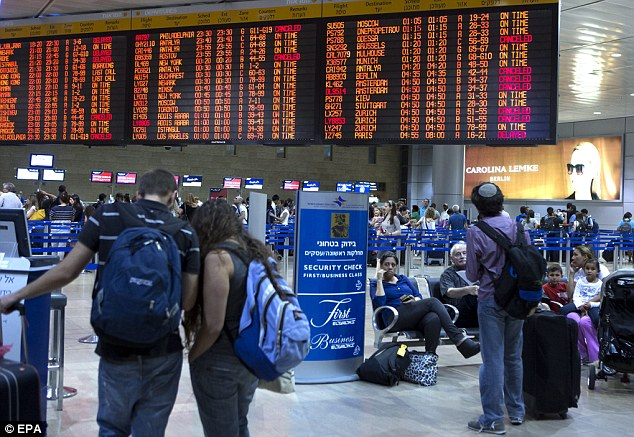 Seeing red: Passengers check the board as it listing departing flights  and those cancelled (in red) at the departure area of Ben Gurion Airport, in Lod, Israel, outside Tel Aviv as many carriers choose to cancel flights for up to 36 hours