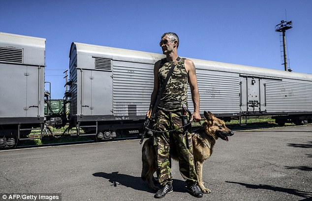 An armed pro-Russian separatists stands guard in front of wagons containing the remains of victims from the downed Malaysia Airlines Flight MH17, at a railway station in the eastern Ukrainian town of Torez on 21 July. There are fears that up to a third of the passengers remain unaccounted for at the crash site