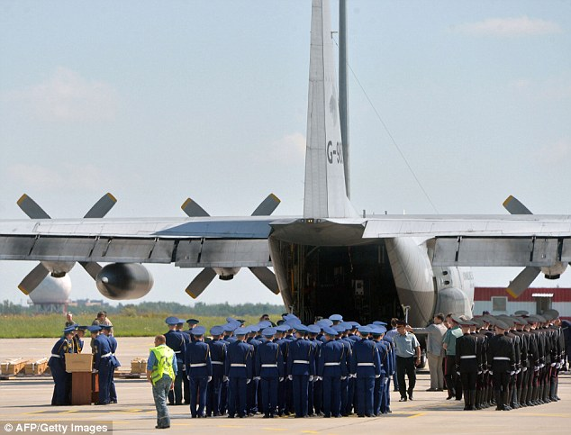 Ukrainian servicemen carry a coffin that contains a body from MH17 during a ceremony in Kharkiv today.The Dutch military aircraft took off from the airport in the government-controlled city of Kharkiv bound for Eindhoven after the first group of victims' remains were loaded onto the plane in wooden coffins