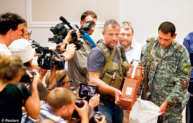 Display: A pro-Russian separatist shows members of the media a black box recorder belonging to flight MH17, before its handover to Malaysian representatives in Donetsk. British experts will now carry out the analysis