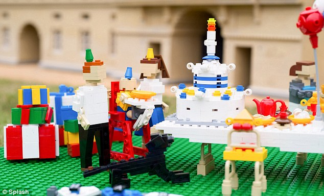 Ah isn't he sweet! The Royal one-year-old flanked by his parents si recreated sitting in his highchair ready for a Lego cake