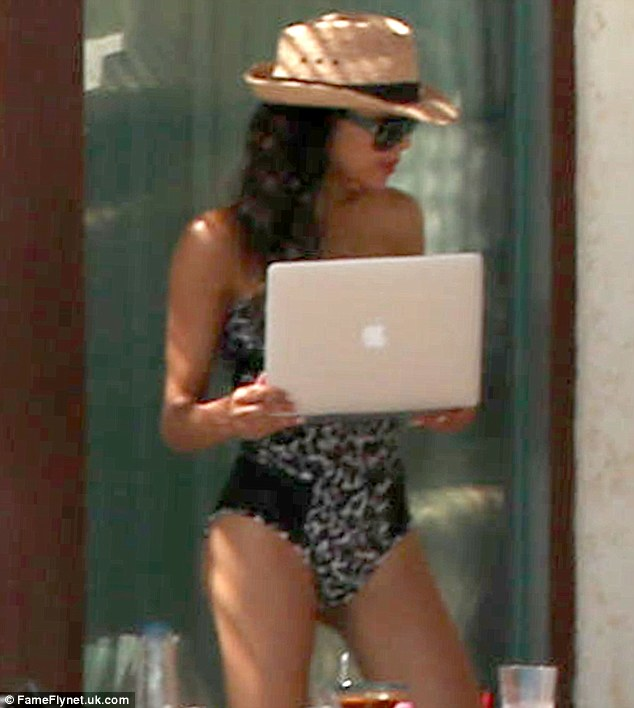 Reading up: Naya clutched a laptop as she appeared to check something in her cabana