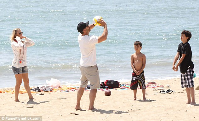 Blending families: LeAnn Rimes has taken to the role of step-mother to Eddie Cibrian's sons Mason and Jake, seen here in April playing on the beach in Ventura, California