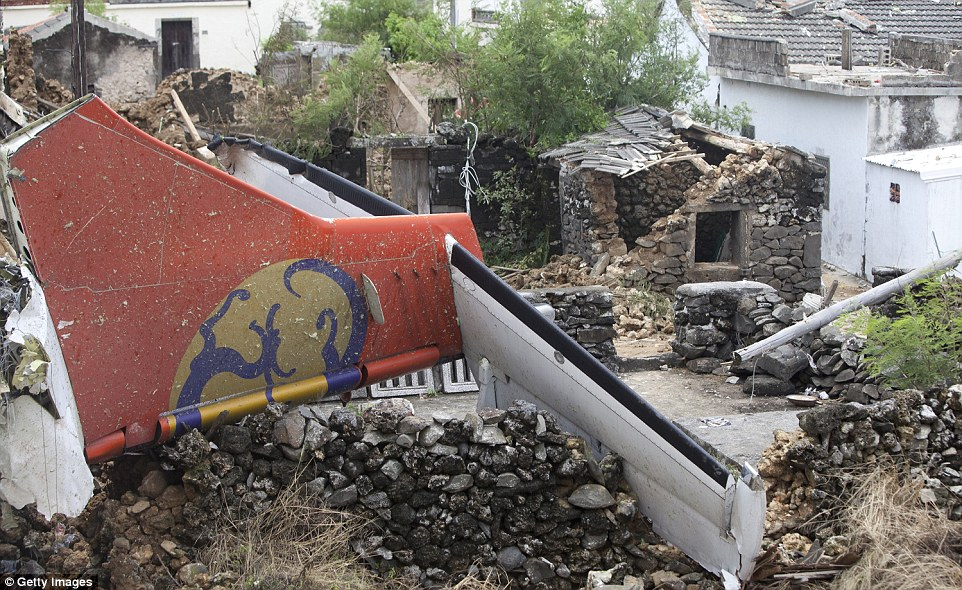 The tail of TransAsia Airways flight GE222 is seen after it fell on a local house the night before