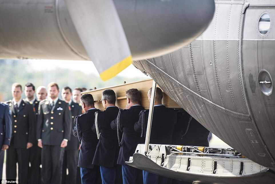 Sombre: The military planes arriving in Eindhoven today were greeted with a minute of silence as coffins were unloaded and placed in the back of waiting hearses