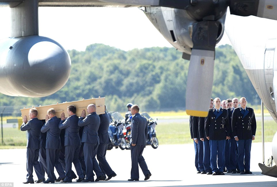 Care: Coffins containing the remains of MH17 victims are removed from a transport plane at Eindhoven airport yesterday. The dignified reception was in stark contrast to the treatment of the remains in Ukraine